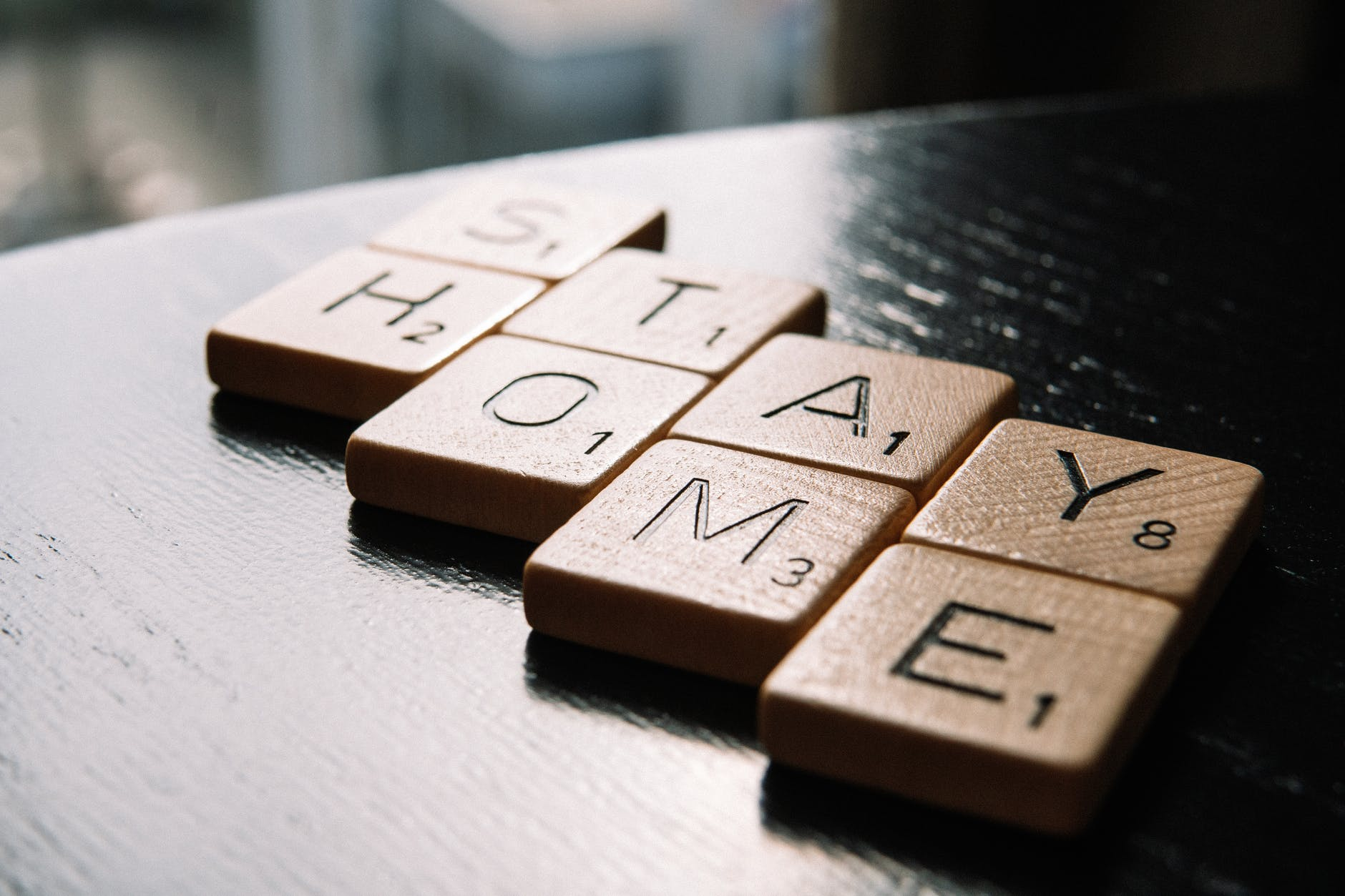 letter tiles arranged in text stay home on table